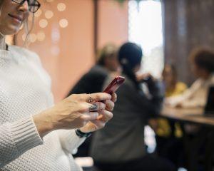 Femme sur son portable dialoguant avec un robot conversationnel